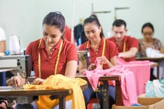 Asian garment fabric workers at work stations