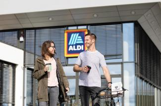 Two customers in front of an ALDI store