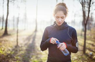 A jogger with a water bottle in a forest