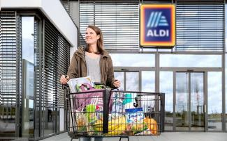 A woman with a filled shopping cart in front of an ALDI store