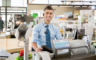 Frontal photograph of an ALDI employee manning the till