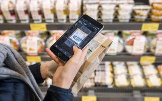 A customer in an ALDI store scanning the QR code of a product
